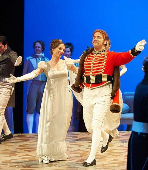 Peter Barrett on stage wearing a red and white Russian military uniform and smiling broadly as he strides forward in a happy ball scene from Prokofiev's opera War and Peace.