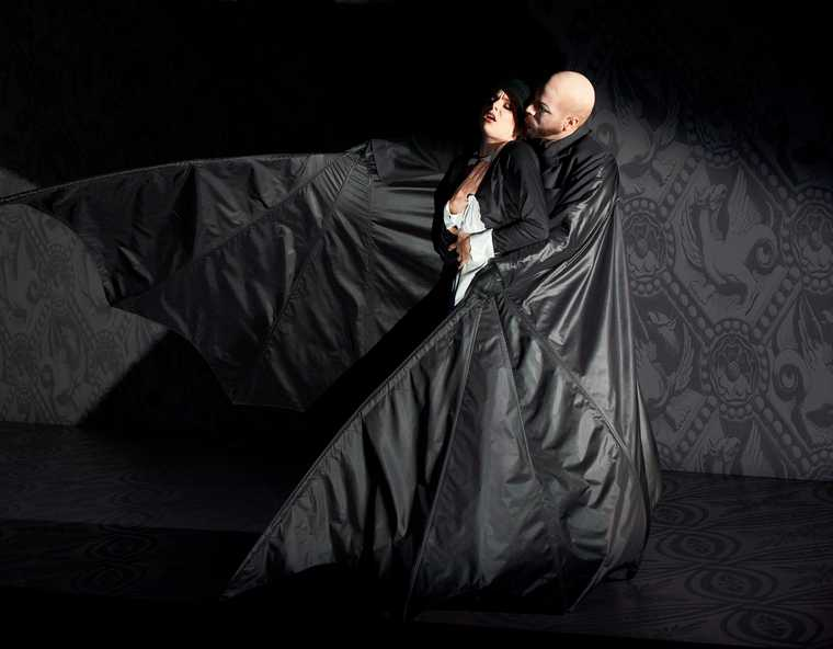 Peter Barrett in a small black room, dressed in a full-body black leather bat costume, with his arms and wings around a woman with a concerned expression on her face.