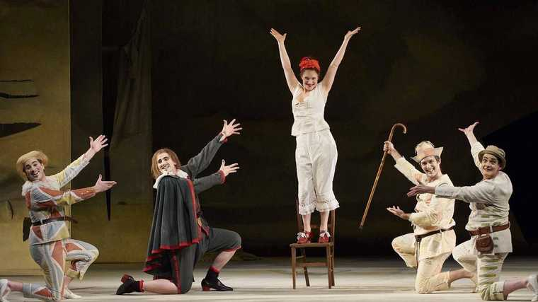 Peter Barrett on stage with four other performers, performing a song and dance number dressed as Harlequin in Ariadne auf Naxos.